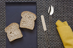 Plaat met brood en servetlepelmes op afwijkingsachtergrond Royalty-vrije Stock Afbeeldingen