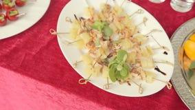 Plaat met canapes die uit garnalen en ananas, fruitplaat op catering bestaan stock footage