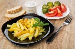 Plaat met gebraden aardappels, tomaten, spruitjes, zout, bre stock fotografie