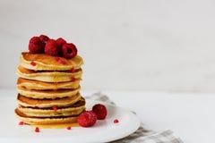 Plaat met heerlijke pannekoeken met frambozen en bessensaus op witte achtergrond Lege boekdekking royalty-vrije stock foto