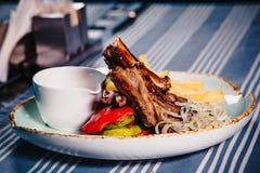 Plaat met rek van lam, geroosterde groenten en frieten Clouse omhoog royalty-vrije stock afbeelding