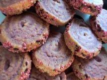 Plaat met shortcrustkoekjes dat wordt gevuld met spiraalvormig patroon, dat met roze gekleurde zaden aan de kanten wordt verfraai royalty-vrije stock foto's