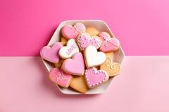 Plaat met verfraaide hart gevormde koekjes op kleurenachtergrond, hoogste mening De dag van de valentijnskaart `s stock fotografie