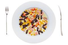 Plaat met voedselsupplementenpillen stock afbeelding
