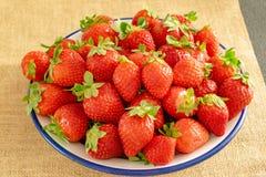 Plaat van aardbeien op textielachtergrond stock foto's