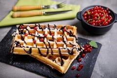 Plaat van Belgische wafels met chocoladesaus en besfruit Stock Foto's
