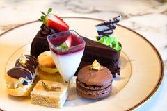 Plaat van buitensporige desserts met inbegrip van donkere chocoladecake en macaron Royalty-vrije Stock Foto's