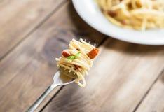 Plaat van Deegwaren Carbonara en Spaghetti met bacon en parmezaanse kaaskaas op een vork op oude houten lijst Stock Foto