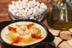 Plaat van hummus en diverse ingrediënten Royalty-vrije Stock Foto's