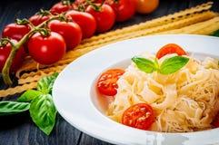 Plaat van Italiaanse deegwaren met tomaten, basilicum en kaas royalty-vrije stock afbeeldingen