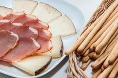 Plaat van kaas en varkensvleeslendestuk Stock Afbeeldingen