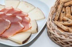Plaat van kaas en varkensvleeslendestuk Stock Afbeelding