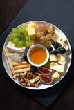 plaat van kazen, snacks en vruchten op een donkere achtergrond Stock Afbeelding