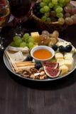 plaat van kazen, snacks, vruchten en wijn op een donkere achtergrond Stock Foto's