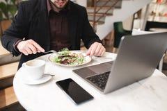 Plaat van salade, laptop, een kop van koffie, een smartphone op de lijst in het restaurant stock foto's