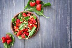Plaat van salade met spinazie, aardbei en okkernoten Stock Fotografie