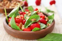Plaat van salade met spinazie, aardbei en okkernoten op lijst, Stock Afbeeldingen