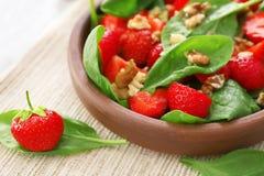 Plaat van salade met spinazie, aardbei en okkernoten op lijst, Stock Afbeelding