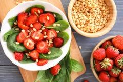 Plaat van salade met spinazie, aardbei en pijnboomnoten Stock Afbeelding
