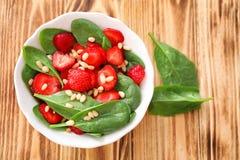 Plaat van salade met spinazie, aardbei en pijnboomnoten Stock Foto