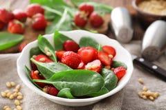 Plaat van salade met spinazie, aardbei en pijnboomnoten Royalty-vrije Stock Afbeeldingen