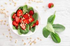 Plaat van salade met spinazie, aardbei en pijnboomnoten Stock Afbeeldingen