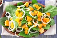 Plaat van salade met spinazie en sinaasappel Royalty-vrije Stock Afbeeldingen