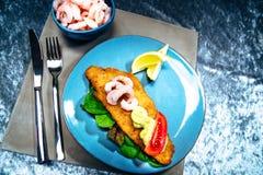 Plaat van visfilet met verse hierboven garnalen, citroenen en groenten van stock foto