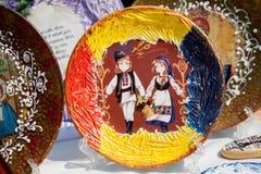 Plaat waar de achtergrond van de Moldovische vlag, de jongen en het meisje met mand van bloemen dragen Stock Foto's