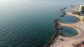 Plaats: De toevlucht van Roemenië, Jupiter, Europa Datum: 03 juli, 2019 Strand met stoelen en paraplu's, golven die de kust raken stock video