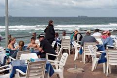 Plaatselijke bewoners en toeristen bij een restaurant op de promenade bij het strand in Umhlanga-Rotsenstrand Stock Afbeelding