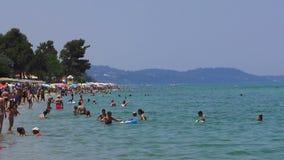 Plaatselijke bewoners en toeristen op een Grieks strand op een hete dag stock footage