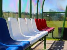 Plaatsen voor bussen en reservespelers op het voetbalgebied Plastiek gekleurde banken onder een luifel van transparante glasvezel stock foto