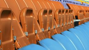 Plaatsingsrijen in stadion met gevouwen stoelen Sluit omhoog lege oranje en blauwe zetels stock video