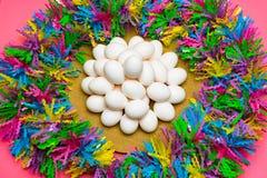 Placa agradable de los huevos de Pascua incoloros con el fondo del color en colores pastel Imágenes de archivo libres de regalías