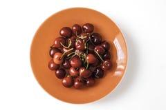 Placa alaranjada completamente de cerejas vermelhas doces imagens de stock royalty free