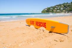 Placa alaranjada do salvamento da ressaca do protetor de vida na areia em Palm Beach, NSW imagem de stock