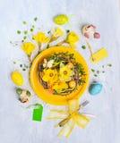 Placa amarela com ovos da páscoa, ninho com flores dos narcisos amarelos e decoração do feriado Fotografia de Stock Royalty Free