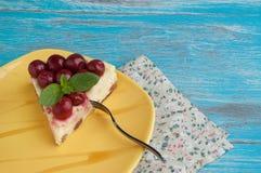 Placa amarilla con un pedazo de pastel de queso Imagenes de archivo