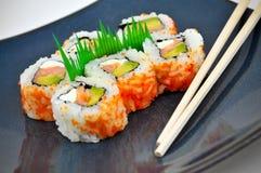 Placa azul con el aperitivo y los palillos del sushi Foto de archivo