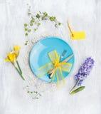 Placa azul con el cuchillo, la bifurcación, las flores de la primavera y la decoración amarilla de la cinta en fondo de madera gr Imágenes de archivo libres de regalías