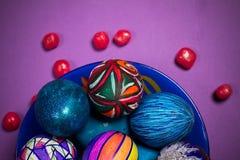 Placa azul con los huevos de Pascua multicolores, caramelos, fondo púrpura Foto de archivo