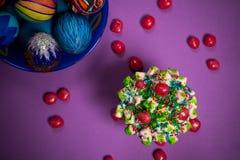 Placa azul con los huevos de Pascua multicolores, caramelos, fondo púrpura Fotografía de archivo