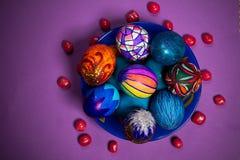 Placa azul con los huevos de Pascua multicolores, caramelos, fondo púrpura Imagen de archivo libre de regalías