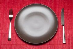Placa, bifurcación y cuchillo vacíos en la estera de bambú Imagen de archivo libre de regalías