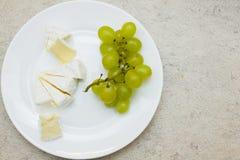 Placa blanca con el manojo de uvas y de pedazos verdes del queso Foto de archivo
