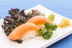 Placa blanca con el nigiri de color salmón con el jengibre y el wasabi foto de archivo