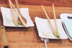 Placa blanca con la cuchara de madera con el polvo del matcha fotografía de archivo libre de regalías