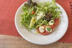 Placa blanca con la ensalada, la lechuga, los tomates, la mozzarella y la albahaca imagen de archivo