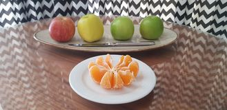 Placa blanca con las rebanadas peladas del mandarín y un plato con cuatro manzanas de diversos colores y de un cuchillo fotografía de archivo libre de regalías